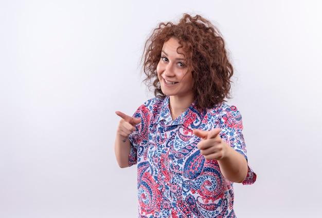 Blij jonge vrouw met kort krullend haar in kleurrijk overhemd glimlachend zelfverzekerd wijzend met wijsvingers naar camera