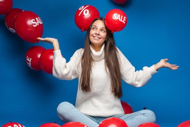 Blij jonge vrouw zitten en kijken op verkoop rode lucht ballonnen, geïsoleerd op blauwe muur
