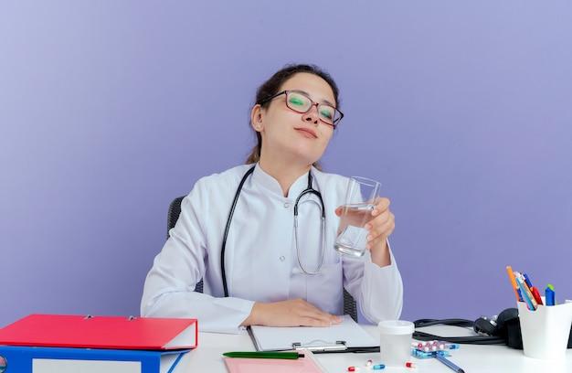 Blij jonge vrouwelijke arts die medische robe en stethoscoopzitting bij bureau met medische hulpmiddelen draagt die geïsoleerd holdingsglas water kijken