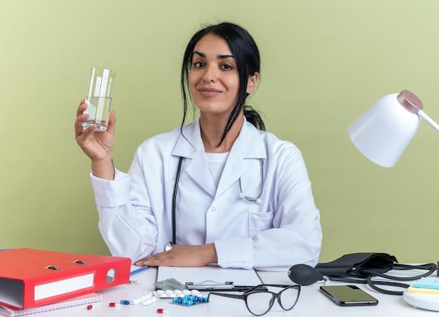 Blij jonge vrouwelijke arts dragen medische gewaad met stethoscoop zit aan bureau met medische hulpmiddelen met glas water geïsoleerd op olijf groene muur