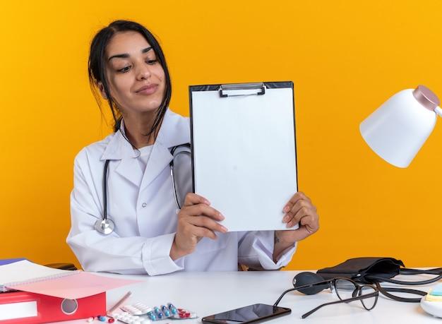 Blij jonge vrouwelijke arts dragen medische gewaad met stethoscoop zit aan tafel met medische hulpmiddelen houden en kijken naar klembord geïsoleerd op gele muur