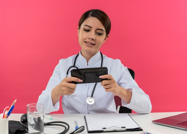 Blij jonge vrouwelijke arts het dragen van medische mantel met stethoscoop zit aan bureau werken op computer met medische hulpmiddelen speelspel op telefoon met kopie ruimte