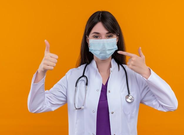 Blij jonge vrouwelijke arts in medische mantel met stethoscoop draagt wegwerp medisch gezichtsmasker duimen omhoog en wijst naar masker op geïsoleerde oranje achtergrond