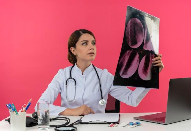 Blij jonge vrouwelijke arts medische gewaad dragen met een stethoscoop zit aan bureau werken op computer met medische hulpmiddelen houden en kijken naar x-ray met kopie ruimte