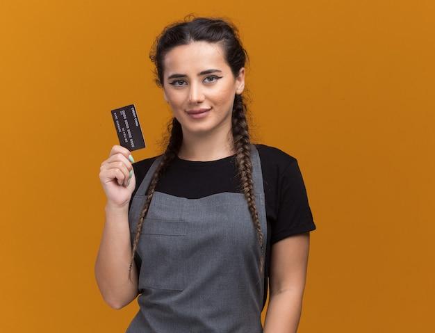 Blij jonge vrouwelijke kapper in uniform bedrijf creditcard geïsoleerd op oranje muur