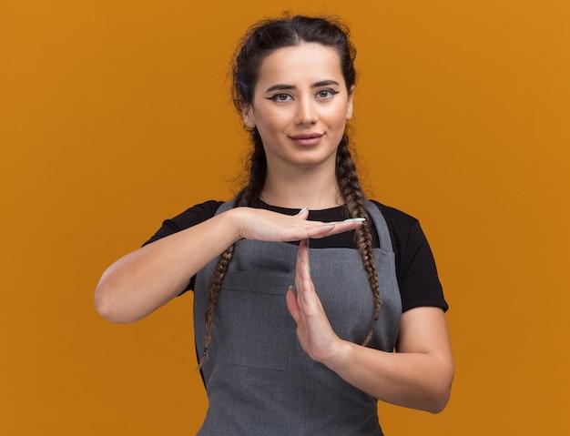 Blij jonge vrouwelijke kapper in uniform met time-outgebaar geïsoleerd op oranje muur