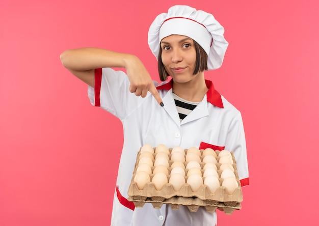 Blij jonge vrouwelijke kok in chef-kok uniform bedrijf en wijzend op karton met eieren geïsoleerd op roze achtergrond