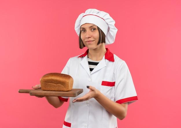 Blij jonge vrouwelijke kok in chef-kok uniforme bedrijf snijplank met brood erop geïsoleerd op roze muur