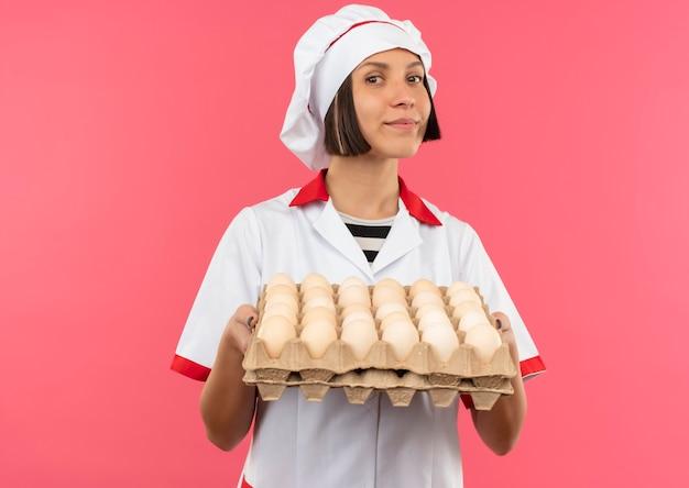 Blij jonge vrouwelijke kok in het karton van de chef-kok het uniforme bedrijf van eieren die op roze achtergrond met exemplaarruimte worden geïsoleerd