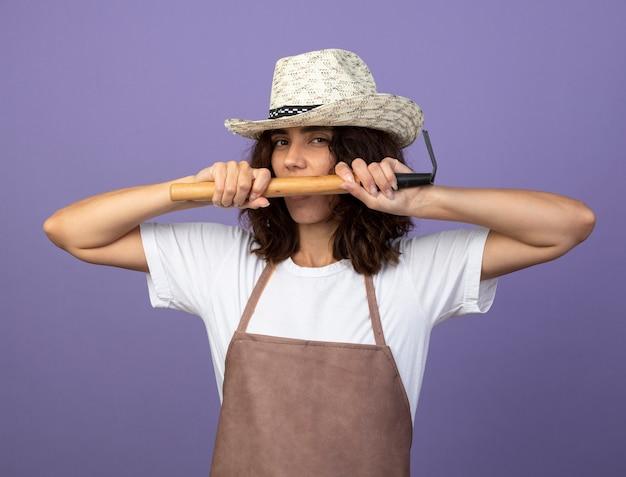 Blij jonge vrouwelijke tuinman in uniform dragen tuinieren hoed met hark rond de mond