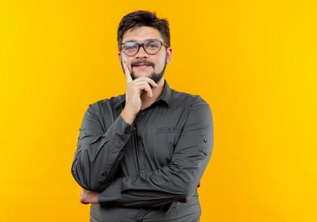Blij jonge zakenman die glazen draagt die hand op kin zetten die op gele achtergrond wordt geïsoleerd