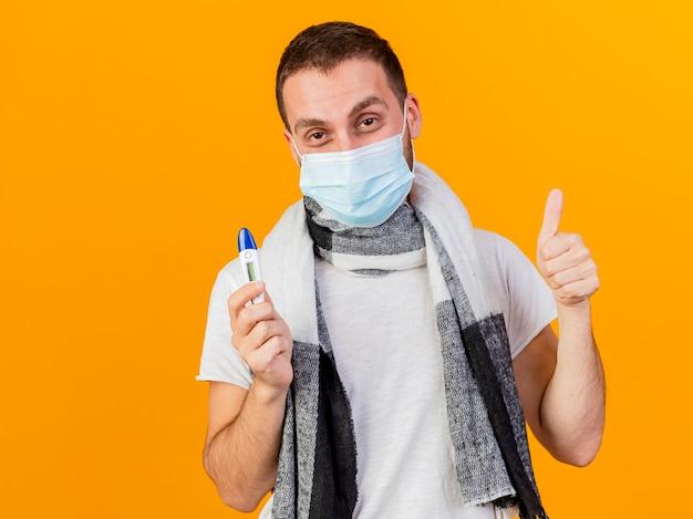 Blij jonge zieke man dragen winter hoed en medische masker houden thermometer weergegeven: duim omhoog geïsoleerd op gele achtergrond