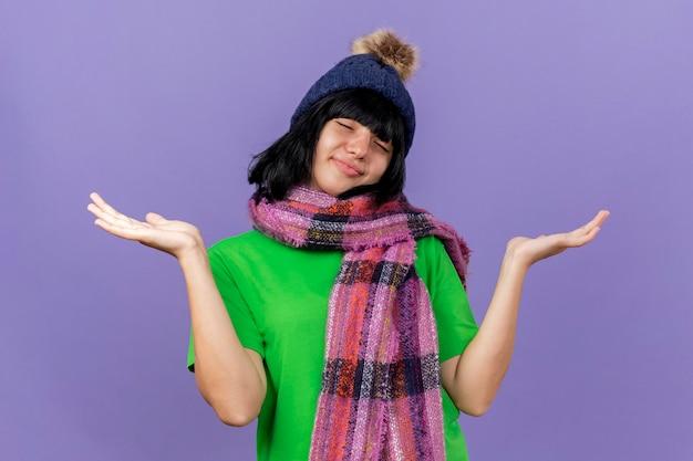 Blij jonge zieke vrouw die de wintermuts en sjaal draagt die lege handen met gesloten ogen toont die op purpere muur worden geïsoleerd