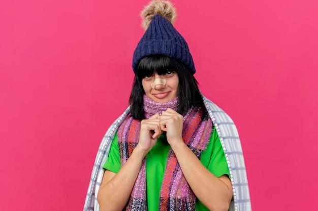 Blij jonge zieke vrouw dragen winter muts en sjaal gewikkeld in plaid kijken voorkant handen samen houden met gips op neus geïsoleerd op roze muur met kopie ruimte
