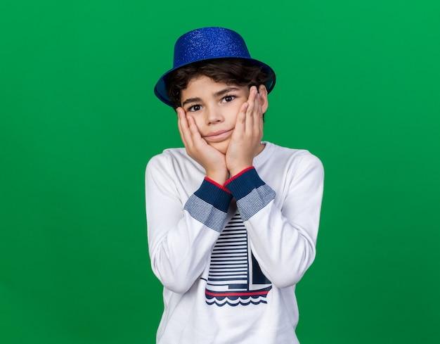 Blij jongetje met blauwe feestmuts bedekte wangen met handen geïsoleerd op groene muur
