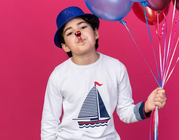 Blij jongetje met een blauwe feestmuts met ballonnen die een feestfluitje blazen
