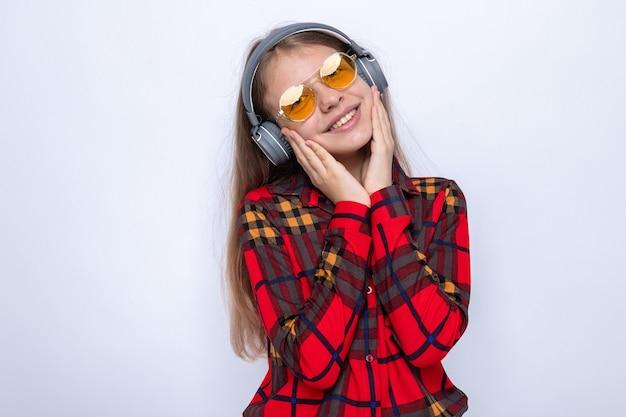 Blij kantelend hoofd handen op wangen leggend mooi klein meisje met rood shirt en bril met koptelefoon