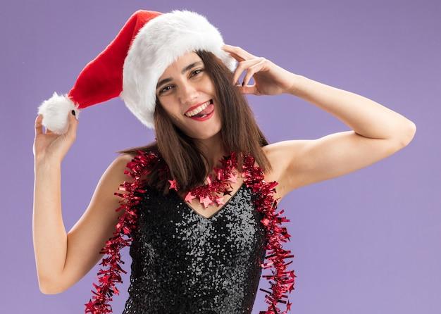 Blij kantelend hoofd jong mooi meisje dat kerstmishoed met slinger op hals draagt die hoed toont die tong toont die op purpere muur wordt geïsoleerd