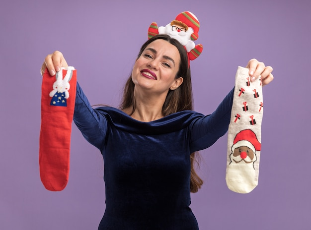 Blij kantelend hoofd jong mooi meisje die blauwe kleding en de hoepel van het kerstmishaar dragen die kerstmissokken houden die op purpere achtergrond worden geïsoleerd