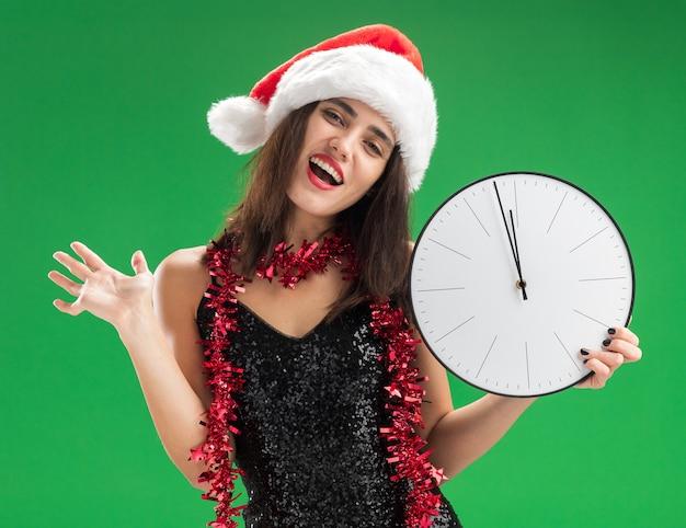 Blij kantelend hoofd jong mooi meisje die kerstmishoed met slinger op hals dragen die muurklok verspreiden die hand op groene muur wordt geïsoleerd