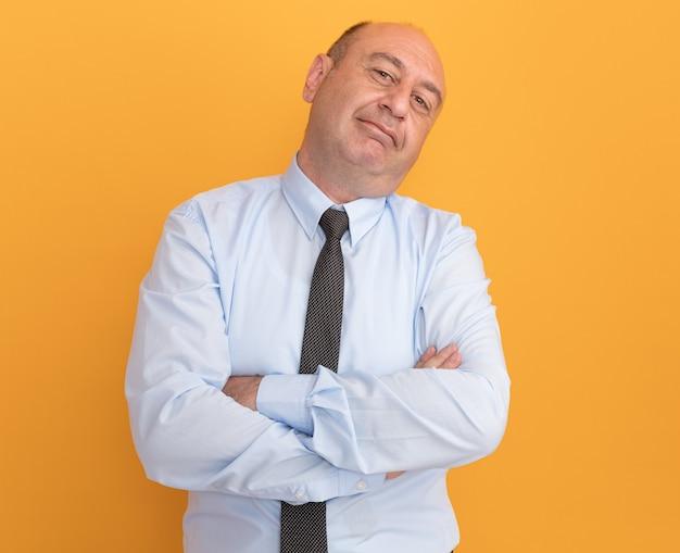 Blij kantelend hoofd man van middelbare leeftijd met een wit t-shirt met stropdas die de handen kruist geïsoleerd op een oranje muur