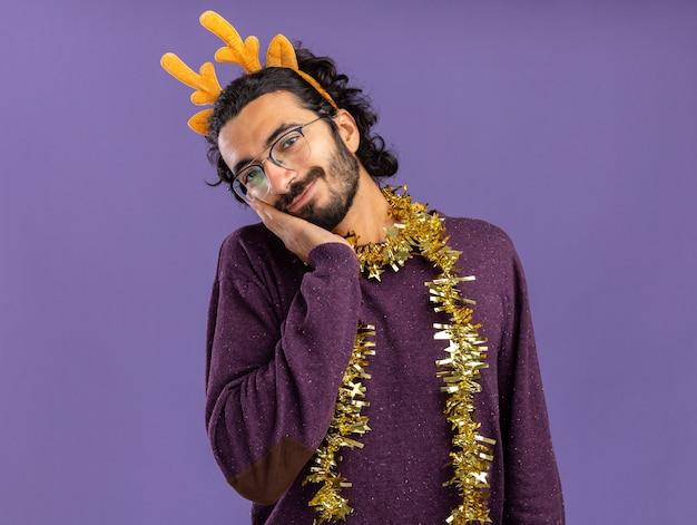 Blij kantelende hoofd jonge knappe kerel met kersthaar hoepel met guirlande op nek hand op wang geïsoleerd op blauwe muur zetten