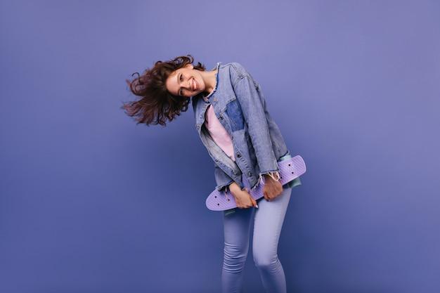 Blij kaukasisch meisje in goed humeur dansen. prachtige gekrulde vrouw met skateboard