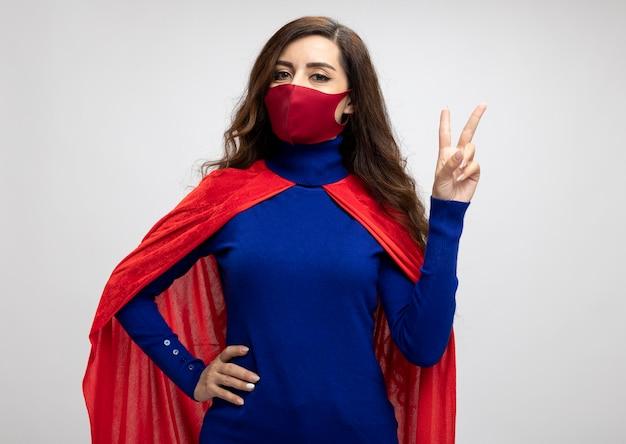 Blij kaukasisch superheromeisje met rode cape die rood beschermend masker draagt