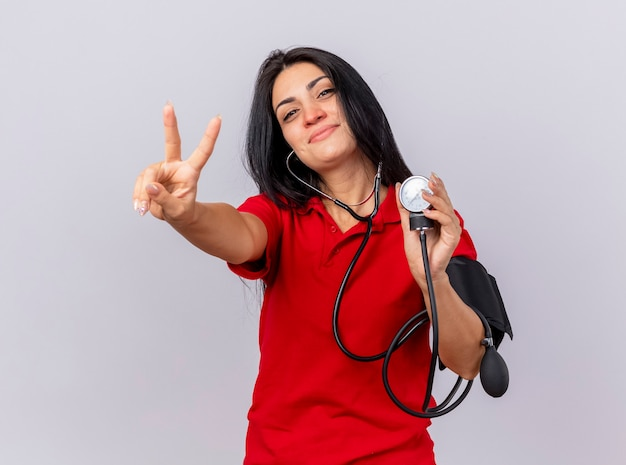 Blij kaukasische ziek meisje dragen stethoscoop kijken camera haar druk meten met bloeddrukmeter doen vredesteken geïsoleerd op witte achtergrond