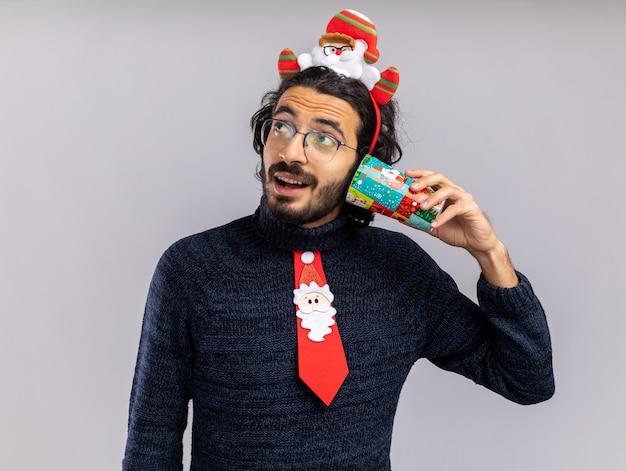 Blij kijken naar kant jonge knappe kerel die kerst stropdas met haar hoepel draagt ?? kerst cup op oor geïsoleerd op een witte achtergrond