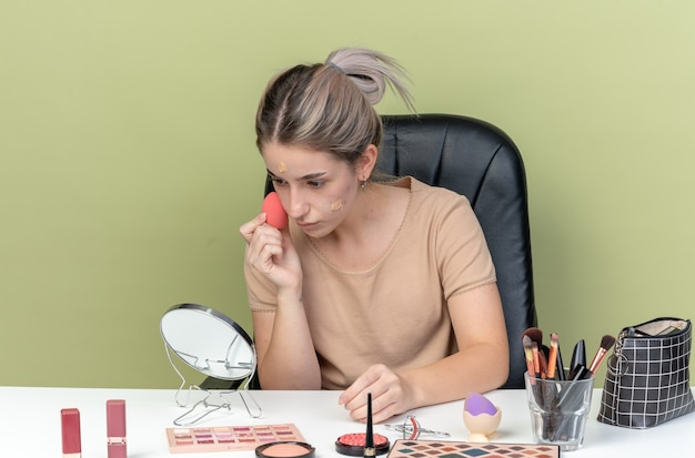 Blij kijken naar spiegel jong mooi meisje zit aan bureau met make-up tools afvegen tone-up crème met spons geïsoleerd op olijf groene muur