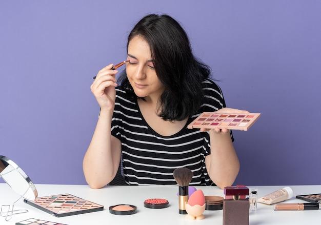 Blij kijken naar spiegel, jong mooi meisje zit aan tafel met make-uptools die oogschaduw toepassen met make-upborstel geïsoleerd op blauwe muur