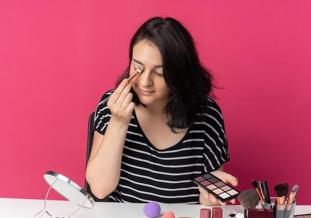 Blij kijken naar spiegel, jong mooi meisje zit aan tafel met make-uptools die oogschaduw toepassen met make-upborstel geïsoleerd op roze muur