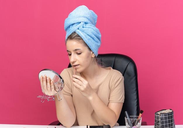 Blij kijken naar spiegel, jong mooi meisje zit aan tafel met make-uptools gewikkeld haar in een handdoek die lipgloss toepast die op roze muur is geïsoleerd