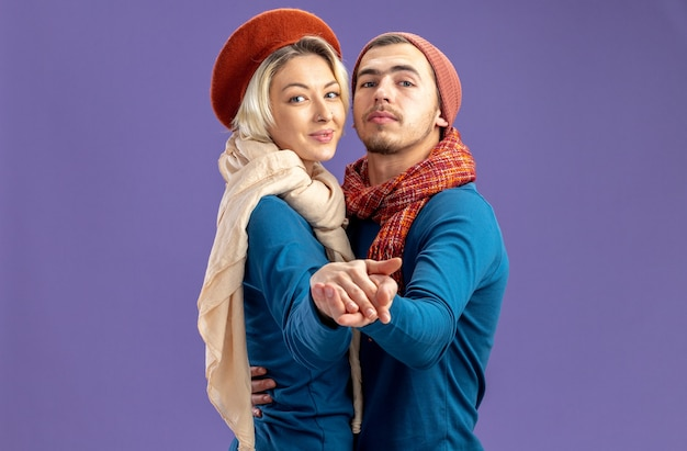 Blij kijkend naar camera jong koppel dragen hoed met sjaal op valentijnsdag dansen geïsoleerd op blauwe achtergrond