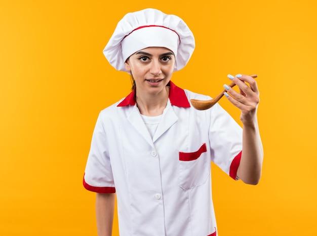 Blij kijkend naar camera jong mooi meisje in chef-kok uniform met lepel