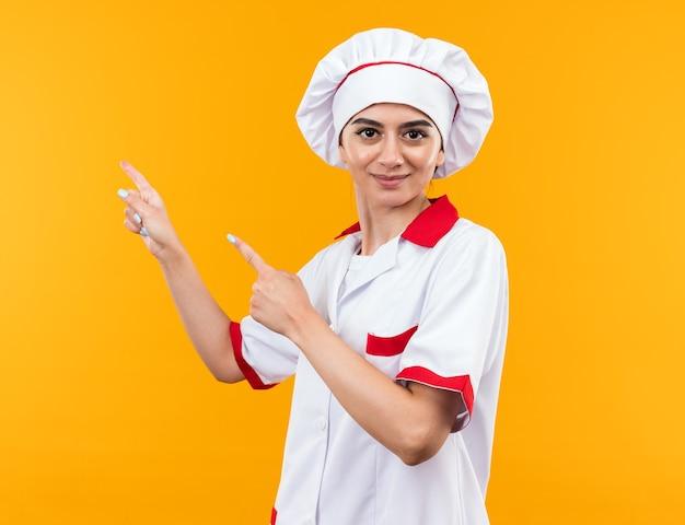 Blij kijkend naar camera, jong mooi meisje in uniform van de chef-kok wijst aan de zijkant