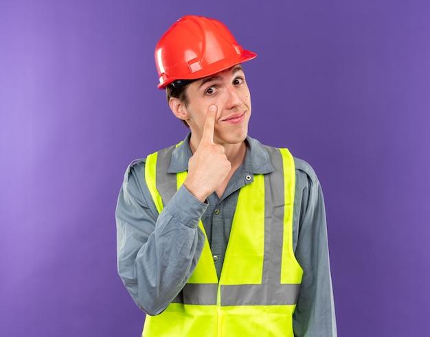 Blij kijkend naar camera jonge bouwman in uniform die oogleden naar beneden trekt