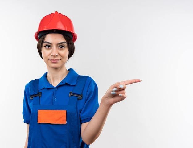 Blij kijkend naar camera jonge bouwvrouw in uniforme punten aan de zijkant