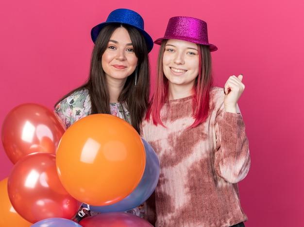 Blij kijkend naar camerameisjes met een feestmuts met ballonnen