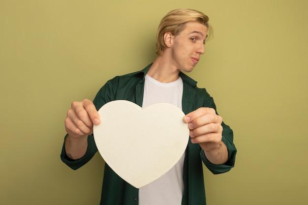Blij kijkend naar de jonge blonde kerel die aan de zijkant een groen t-shirt draagt dat een hartvormdoos vasthoudt