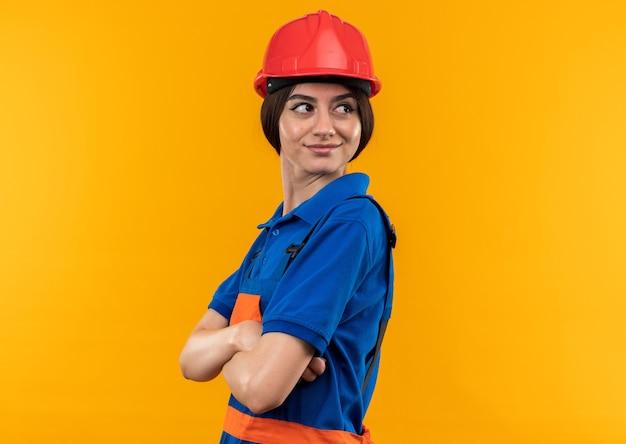 Blij kijkend naar de jonge bouwvrouw aan de zijkant in uniform kruisende handen geïsoleerd op een gele muur met kopieerruimte