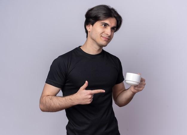 Blij kijkend naar de jonge knappe kerel die aan de zijkant een zwart t-shirt draagt en wijst naar een kopje koffie geïsoleerd op een witte muur