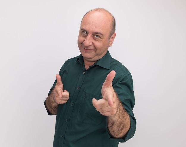 Blij kijkend naar de voorkant man van middelbare leeftijd met groene t-shirt punten aan de voorkant geïsoleerd op een witte muur