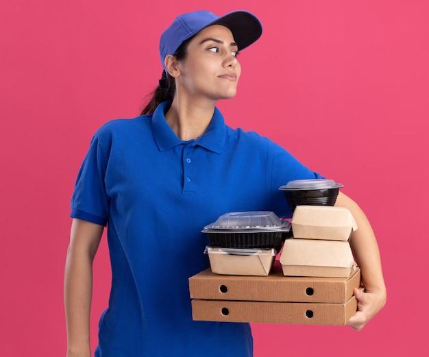 Blij kijkend naar een jong bezorgmeisje aan de zijkant, gekleed in uniform met dop met voedselcontainers op pizzadozen geïsoleerd op roze muur