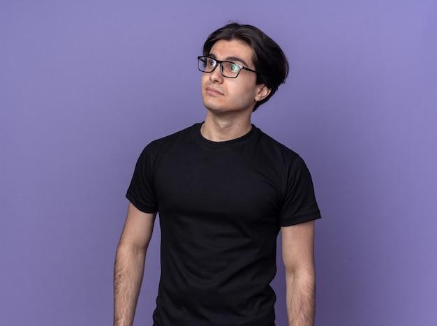 Blij kijkend naar een jonge knappe kerel met een zwart t-shirt en een bril geïsoleerd op een paarse muur
