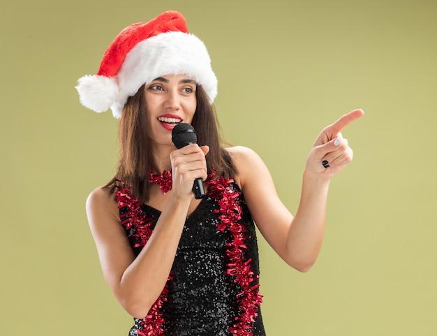 Blij kijkend naar kant jong mooi meisje met kerstmuts met slinger op nek met microfoon en zingt punten aan kant geïsoleerd op olijfgroene achtergrond met kopieerruimte