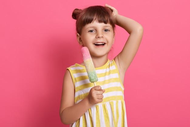 Blij kind eet ijs, houdt haar handen op haar hoofd, vrolijk lachend, staande op een roze muur in een witte en gele zomerjurk.
