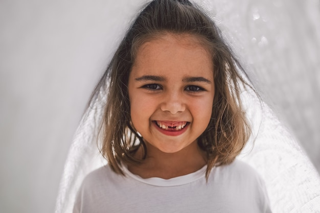 Blij kind. grappig meisje speelt met een deken. glimlachend kindmeisje. vrolijk kind buiten in de natuur