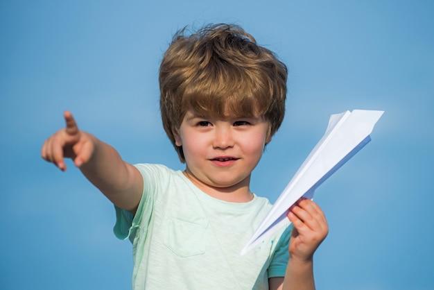 Blij kind. leuke jongen met papier aipplene. gelukkig kind met papieren speelgoed vliegtuig camera kijken. jeugd concept. dromen van reizen. gelukkig kind op zomerveld - droom van vliegend concept.
